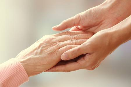 36361867-old-and-young-holding-hands-on-light-background-closeup